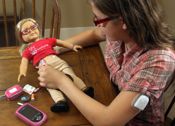 Anja Busse, 13, plays with her American Girl doll, Alice, and her diabetes care kit at her home